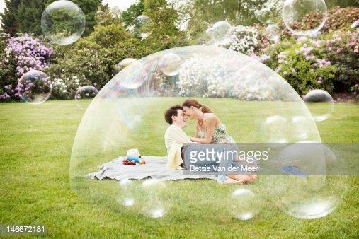 Couple having picnic surrounded by bubbles. : Foto de stock