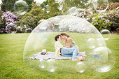 Couple having picnic surrounded by bubbles.