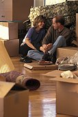 Couple Having Pizza Dinner While Surrounded By Moving Boxes