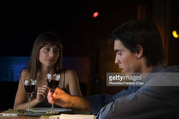Couple having serious conversation over dinner at restaurant, man picking up glass of wine