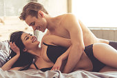 Beautiful young couple is looking at each other and smiling while having sex on bed