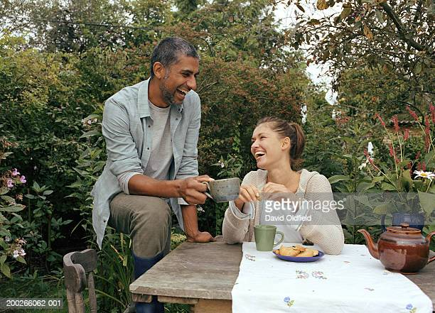 Couple having tea at garden table, laughing