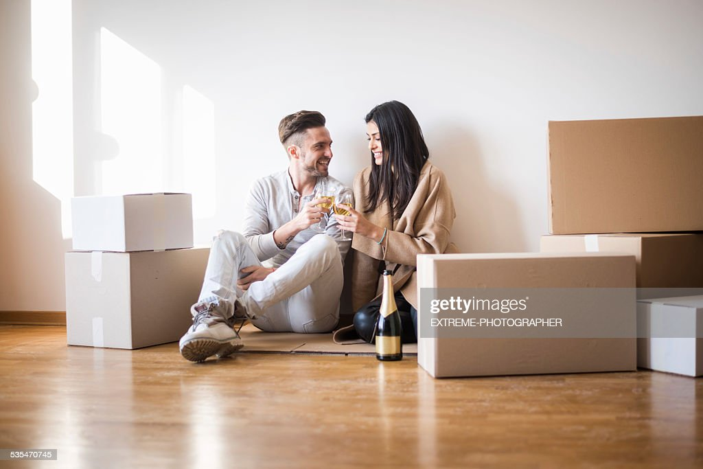 Couple having toast on the floor of new apartment