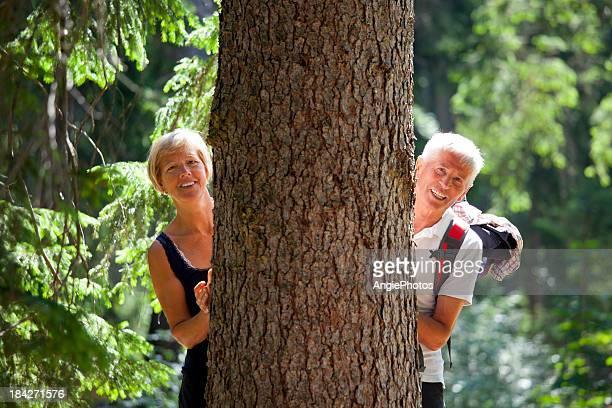 Paar versteckt sich hinter einem Baum im Wald
