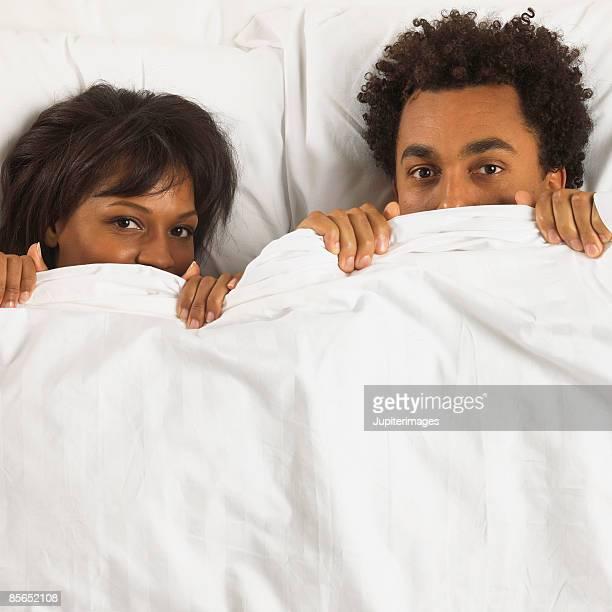 Couple hiding behind bedspread
