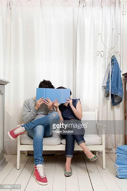 Couple hiding behind books