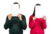 Couple hiding faces with documents while standing on white background