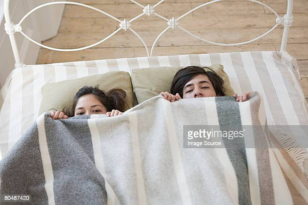 Couple hiding in bed