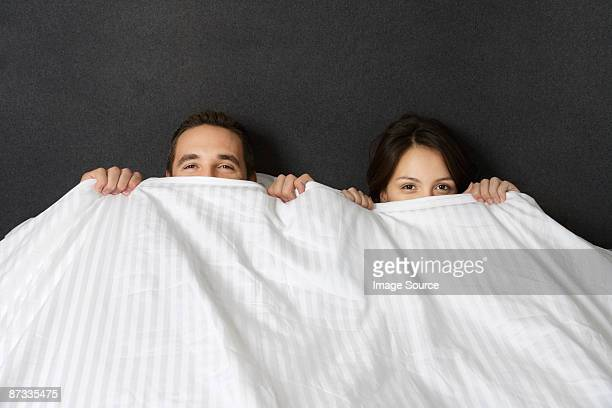 A couple hiding under a duvet