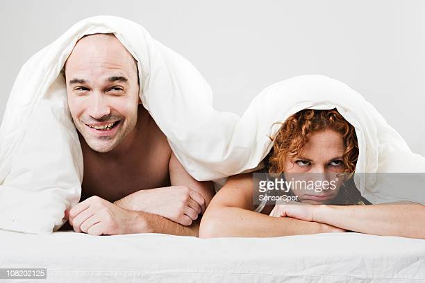 Couple Hiding Under Covers in Bed