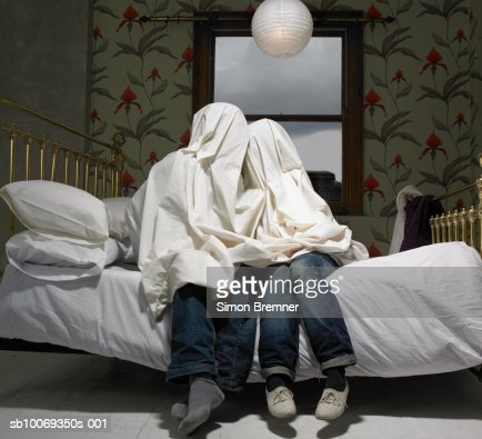 Couple hiding under sheet on bed : Stock Photo