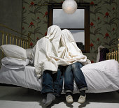 Couple hiding under sheet on bed