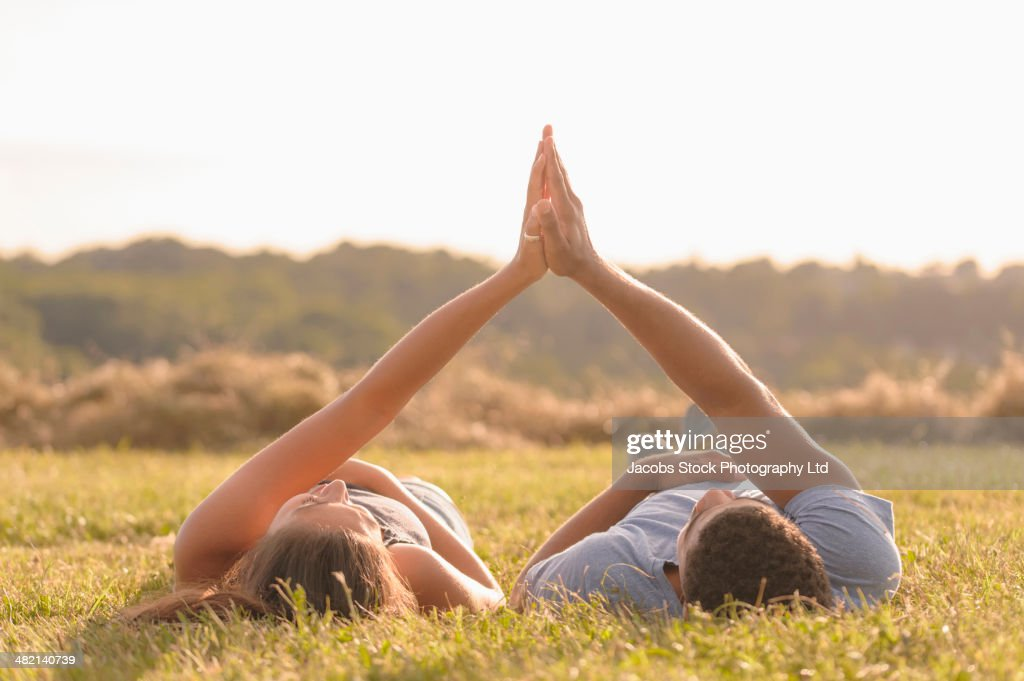 Couple high fiving in grass