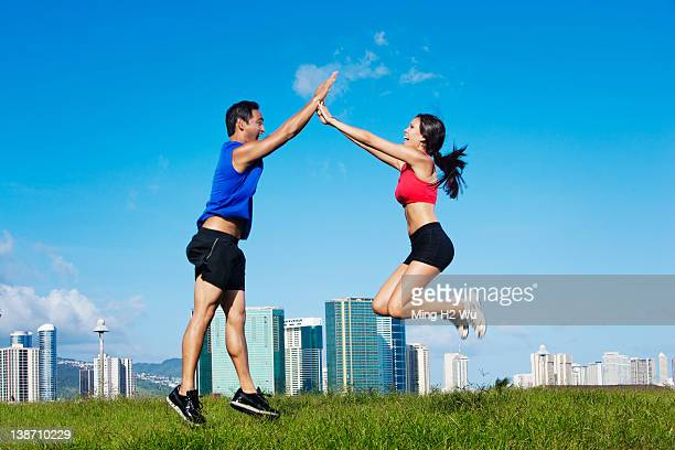 Couple high-fiving in field