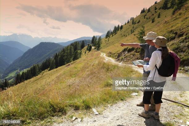 Couple Hiker Pointing At View While Standing In The Alps