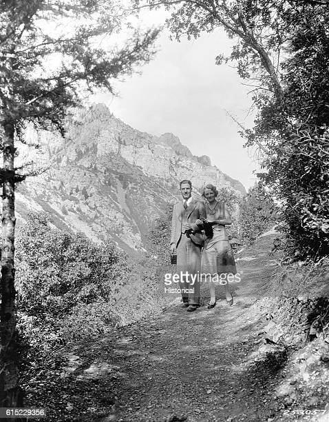 A couple hiking along the Timpanogos Cave trail in the Wasatch National Forest The man carries a box camera Utah | Location Timpanogos Cave Trail...