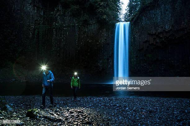 A couple hiking near a waterfall.