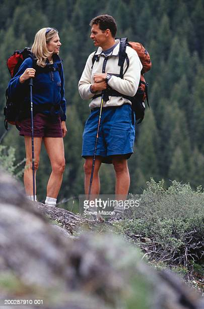 Couple hiking on rugged terrain in mountains