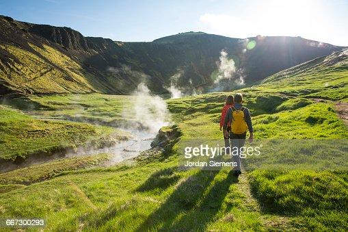A couple hiking through a lush green valley.