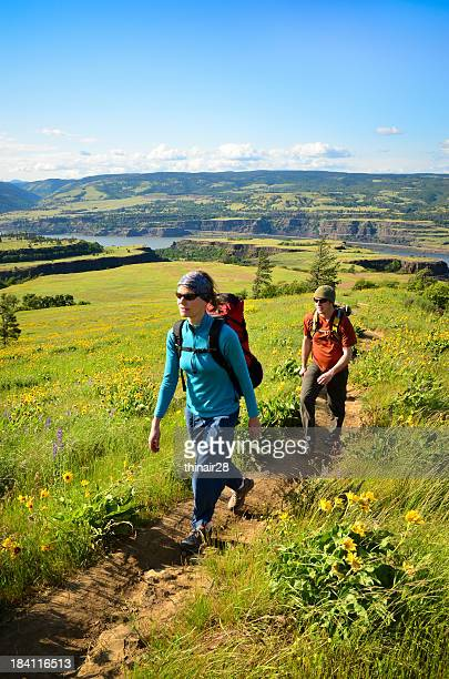 Couple hiking through flowery meadow