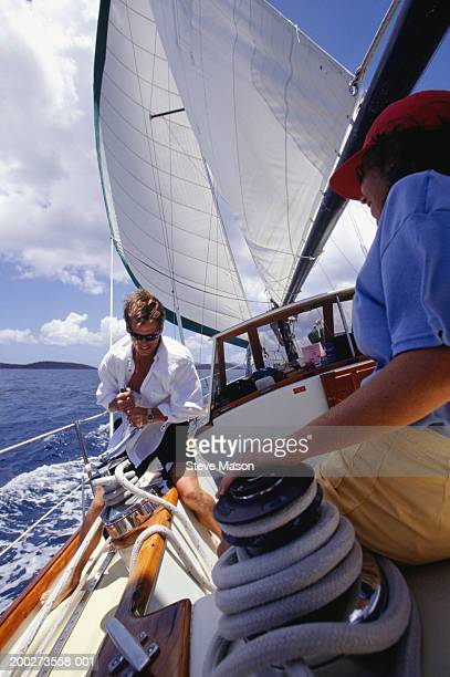 Couple hoisting sail on deck of boat