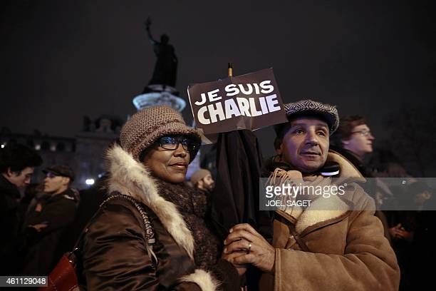 A couple hold a placard reading in French 'I am Charlie' during a gathering at the Place de la Republique in Paris on January 7 following an attack...