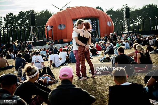 A couple hold each other during the Roskilde Festival on July 3 2013 in Roskilde Denmark The Roskilde Festival is one of the largest annual music...