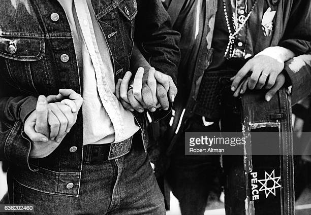 A couple hold hands and carry a guitar with Peace signs during 'The March on Washington' on October 21 1967 in Washington DC