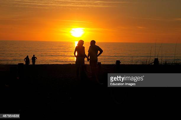 A couple hold hands as the sunsets in Englewood Florida on the beach