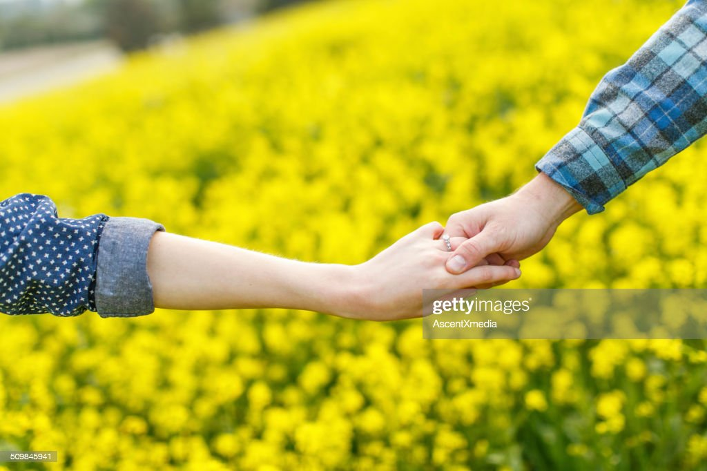 Couple hold hands, display engagement band