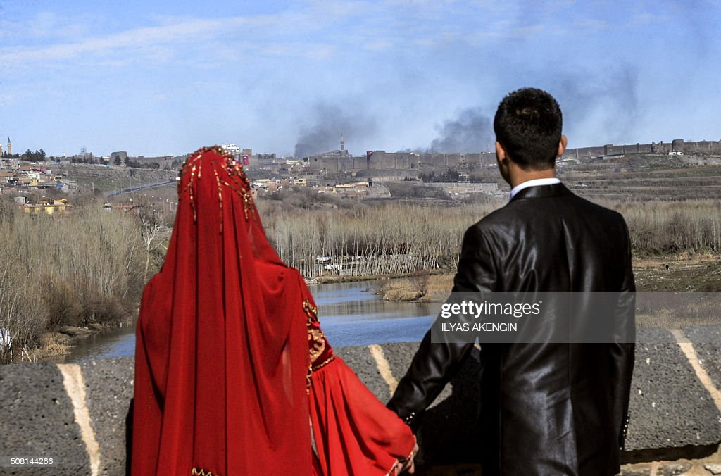 TOPSHOT A couple hold hands for a wedding photo as they look at smokes rising over the district of Sur in Diyarbakir on February 3 2016 after clashes...
