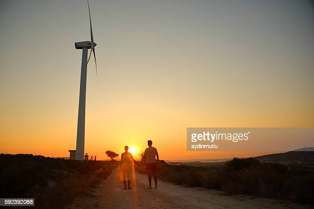 Couple hold hands on Wind turbine