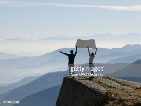 Couple hold placard hgh above distant mountains : Stock Photo