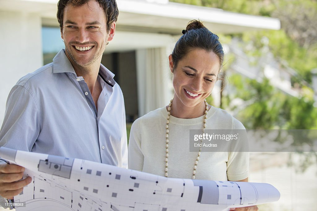 Couple holding a blueprint and smiling : Stock Photo