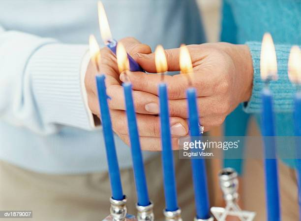 Couple Holding a Lit Candle as Part of a Menorah