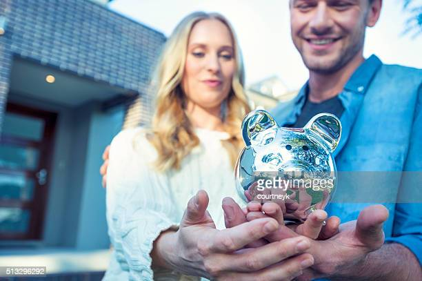 Couple holding a piggy bank in front of house.