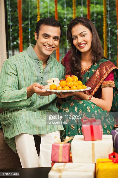 Couple holding a plate of laddoo on Diwali