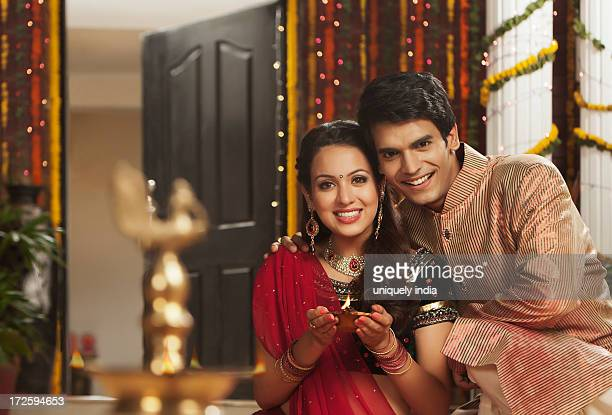 Couple holding an oil lamp on Diwali