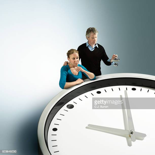 Couple holding baby shoes, looking at large clock