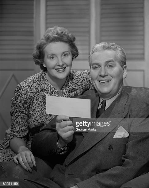 Couple holding bank cheque, indoors, portrait
