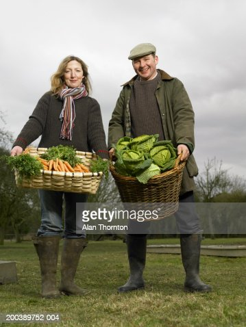Couple holding baskets of carrots and cabbages, smiling, portrait : Stock Photo
