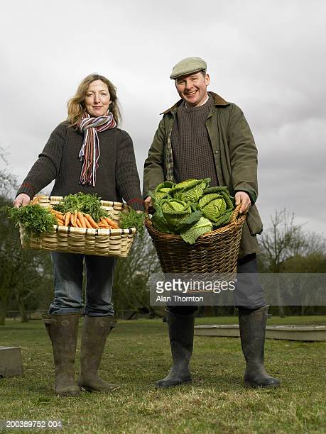 Couple holding baskets of carrots and cabbages, smiling, portrait