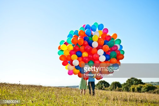 couple holding big bunch of balloons : Stock Photo