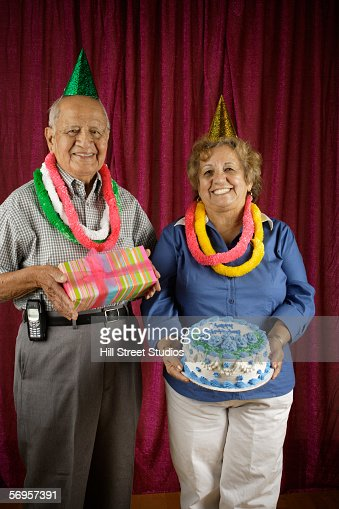 Couple holding birthday cake and present : Stock-Foto