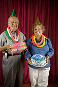 Couple holding birthday cake and present