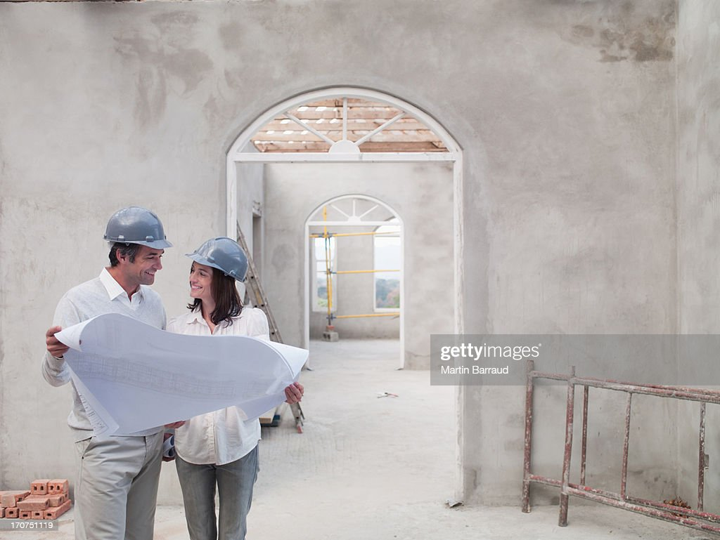 Couple holding blueprints in house under construction : Stock Photo