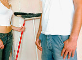 Couple holding brooms