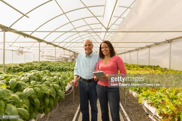 Couple holding clipboard standing in greenhouse