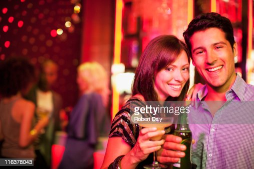 Couple holding drinks in nightclub : Stock Photo