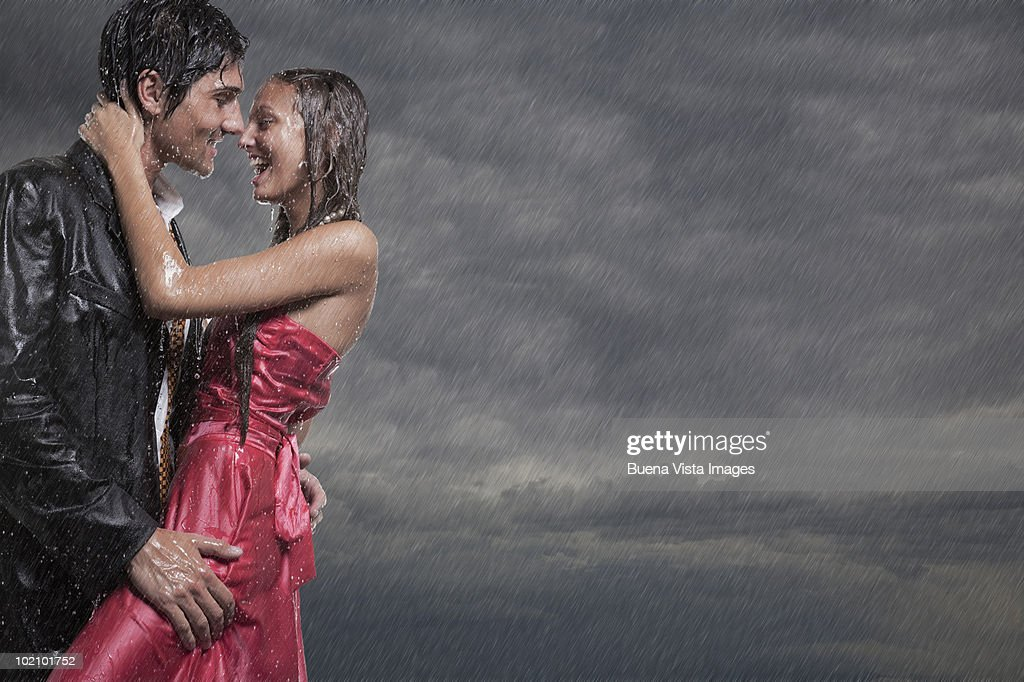 Couple holding each other in rainstorm : Stock Photo